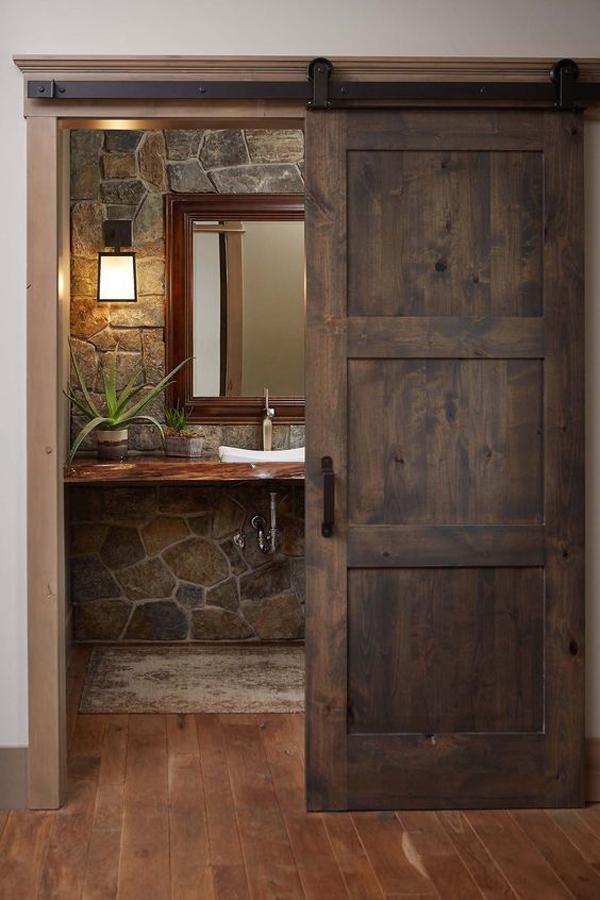 rustic-feel-bathroo-with-stone-wall-and-sliding-barn-door