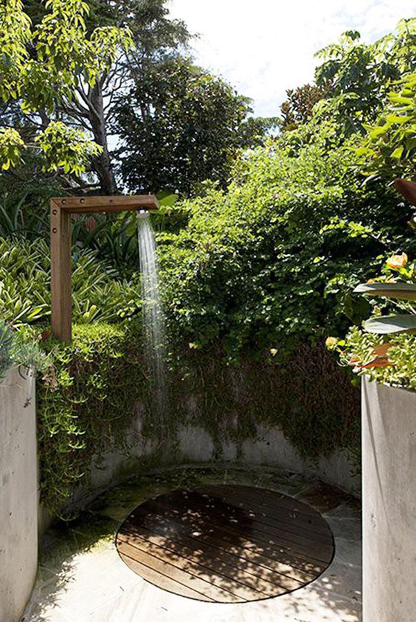 round-outdoor-shower-with-wall-and-plant-barrier