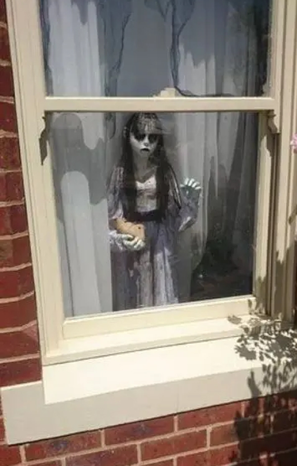 scary-girl-standing-window-decor